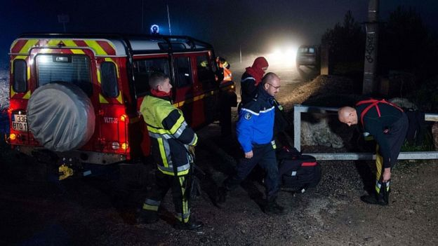 Firefighters and police near the site where a helicopter from the civil security services crashed in the hills in Le Rove, near Marseille early on December 2, 2019